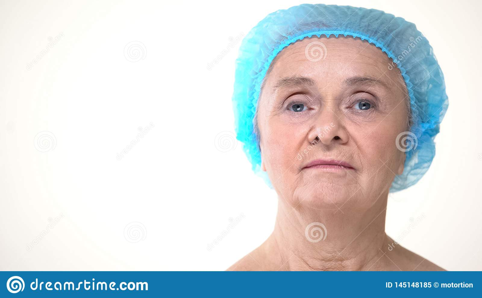 Elderly woman in hygienic cap before cosmetology procedures, plastic surgery