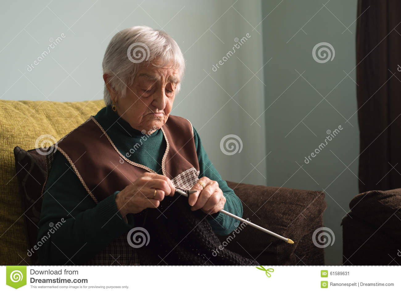 Elderly woman knitting at home.