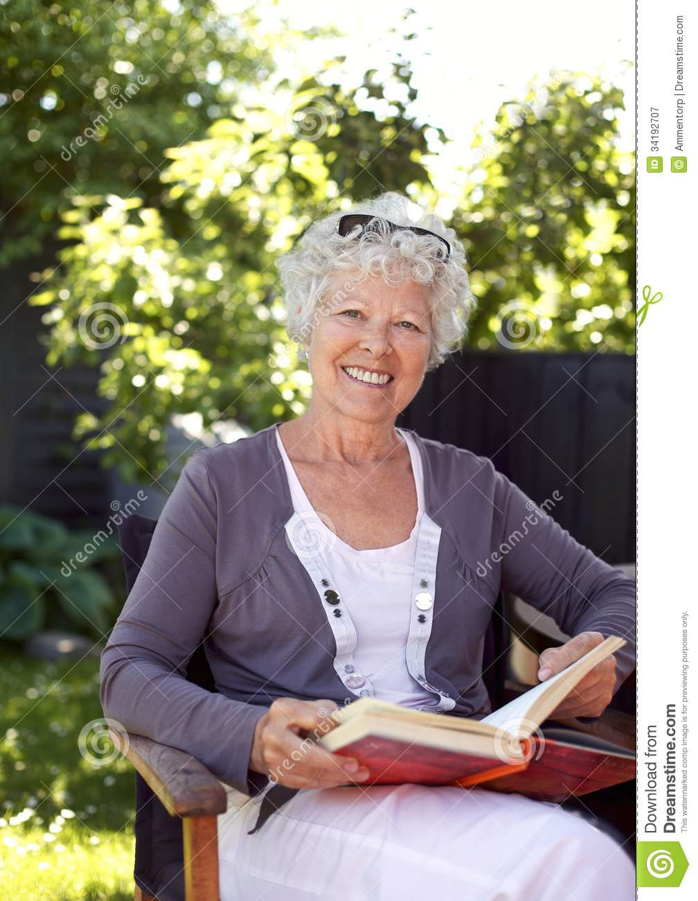 Elderly Woman With Novel In Garden Stock Image Image Of