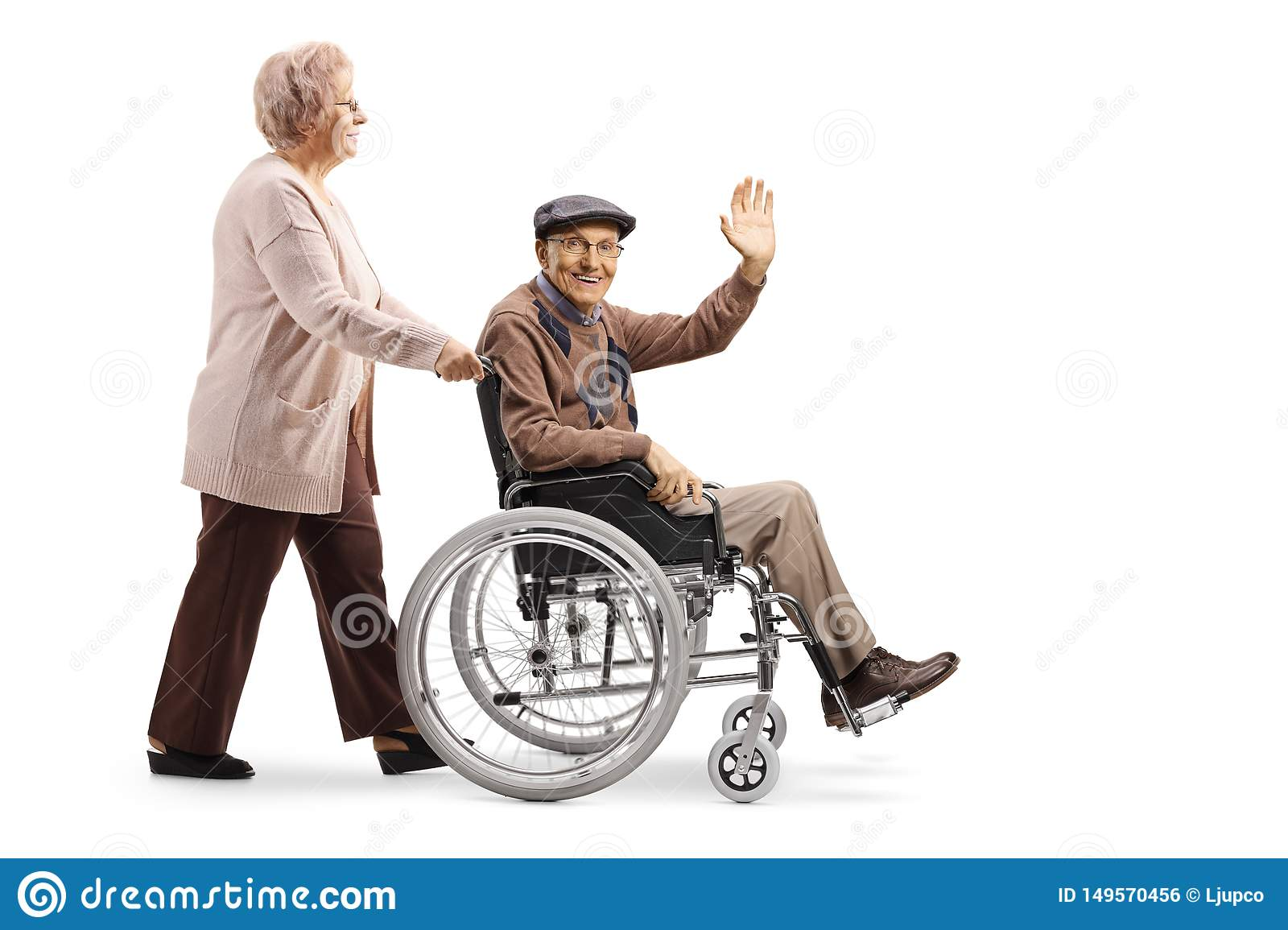 Elderly woman pushing an elderly man waving and sitting in a wheelchair