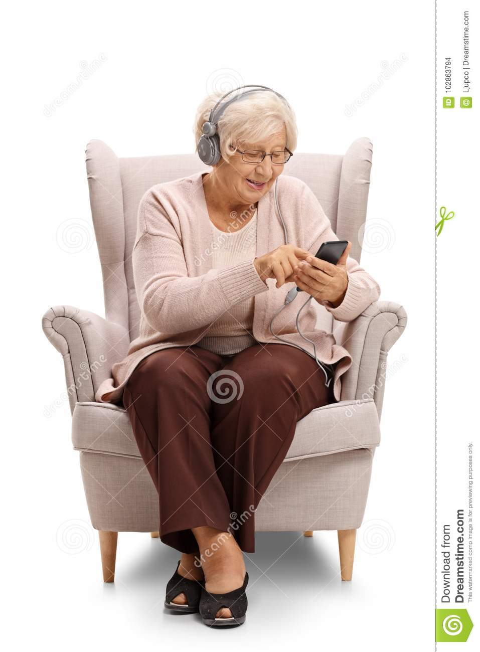 Elderly woman sitting in an armchair and listening to music on a
