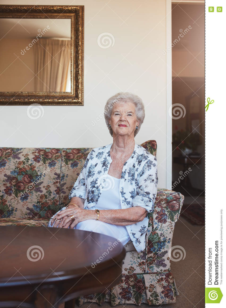 elderly woman sitting on a couch at old age home stock. Black Bedroom Furniture Sets. Home Design Ideas