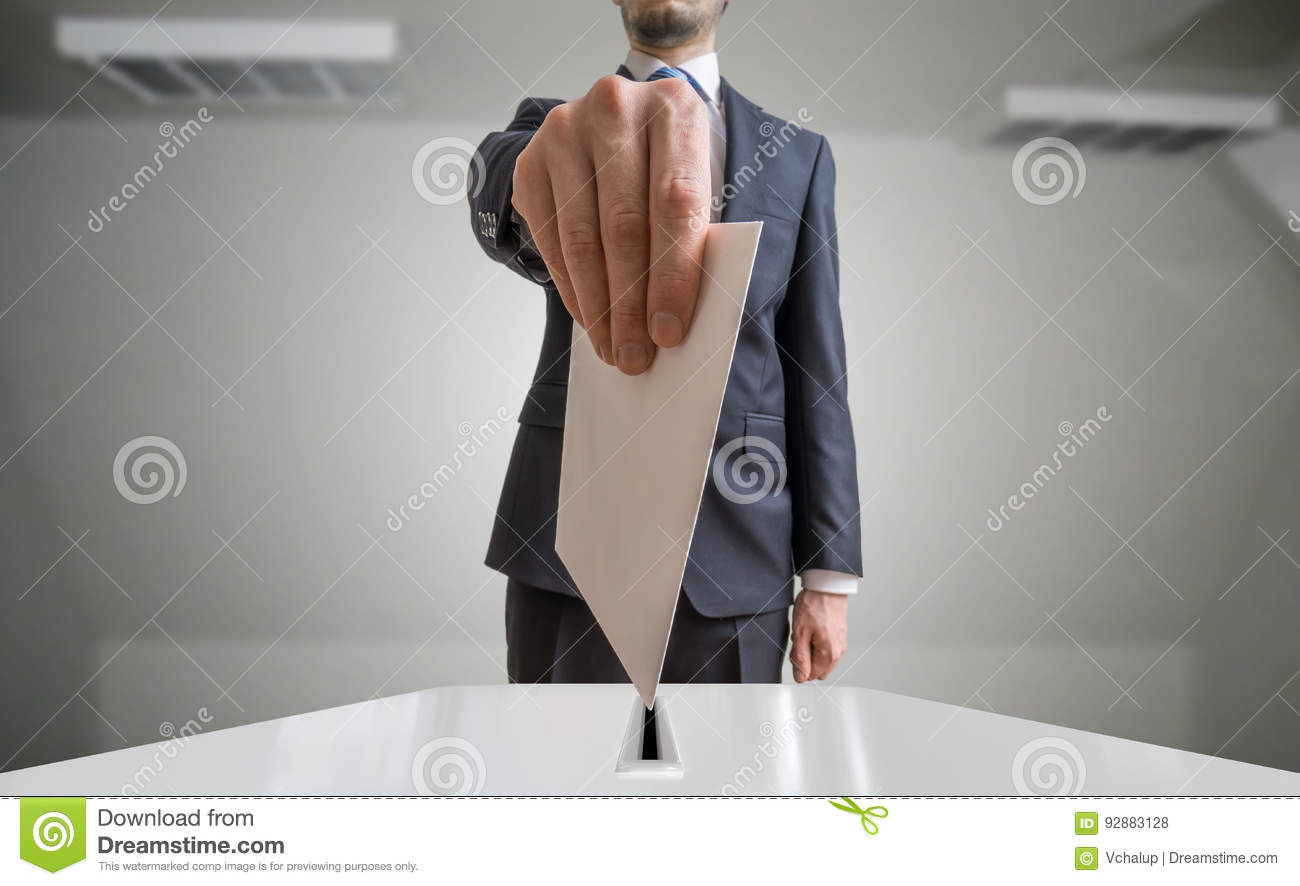 Election and democracy concept. Voter holds envelope or paper in hand above ballot