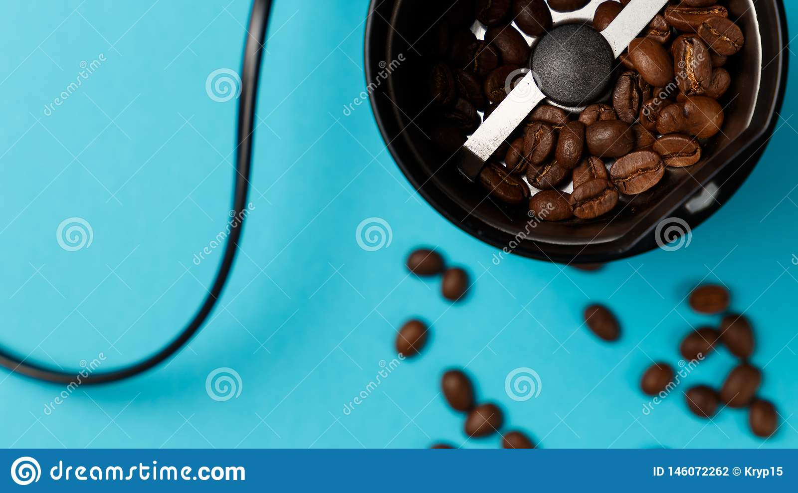 Electric coffee grinder with roasted coffee beans on the kitchen
