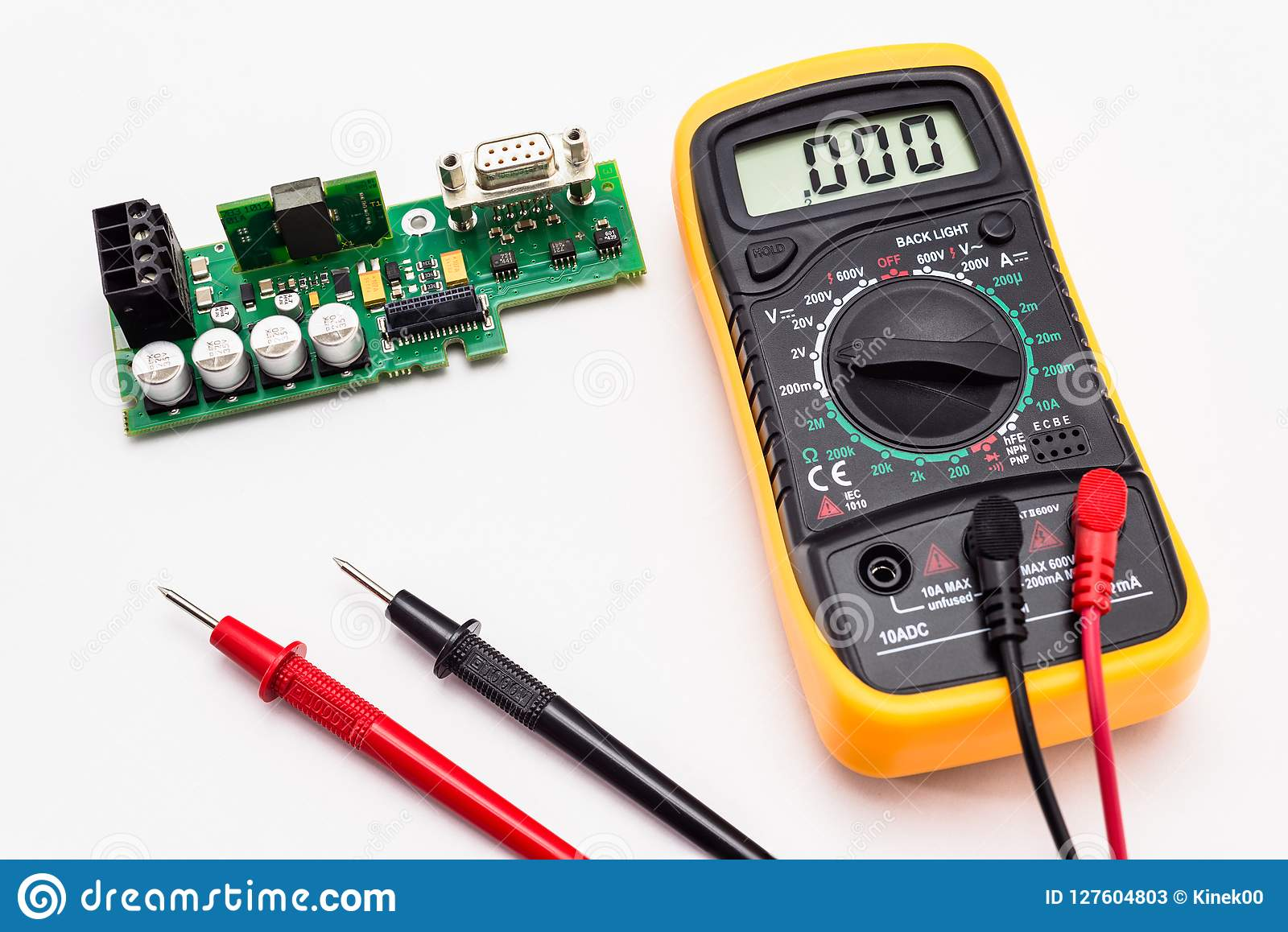 Electric multimeter with red and black probe, display indicating zero, with printed circuit board. Isolated on a white background