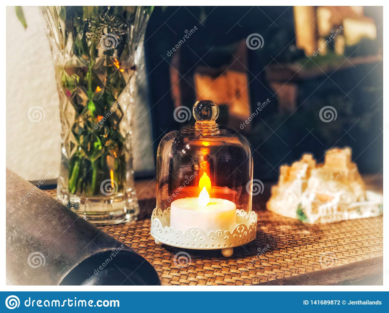 An electric candle burning under a glass on table