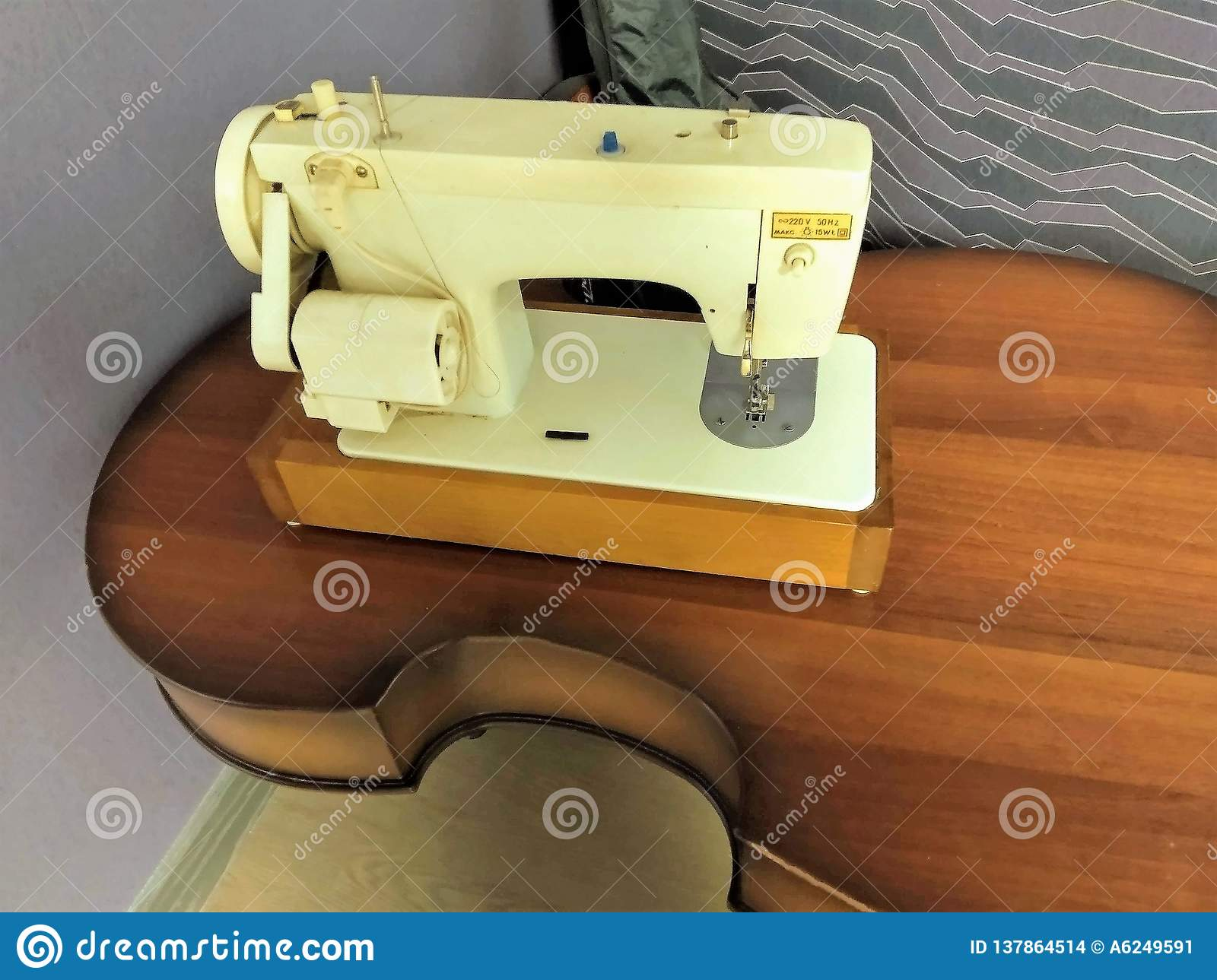 The electric sewing machine of white color costs on a brown wooden table from the old broken contrabass of a musical instrument,
