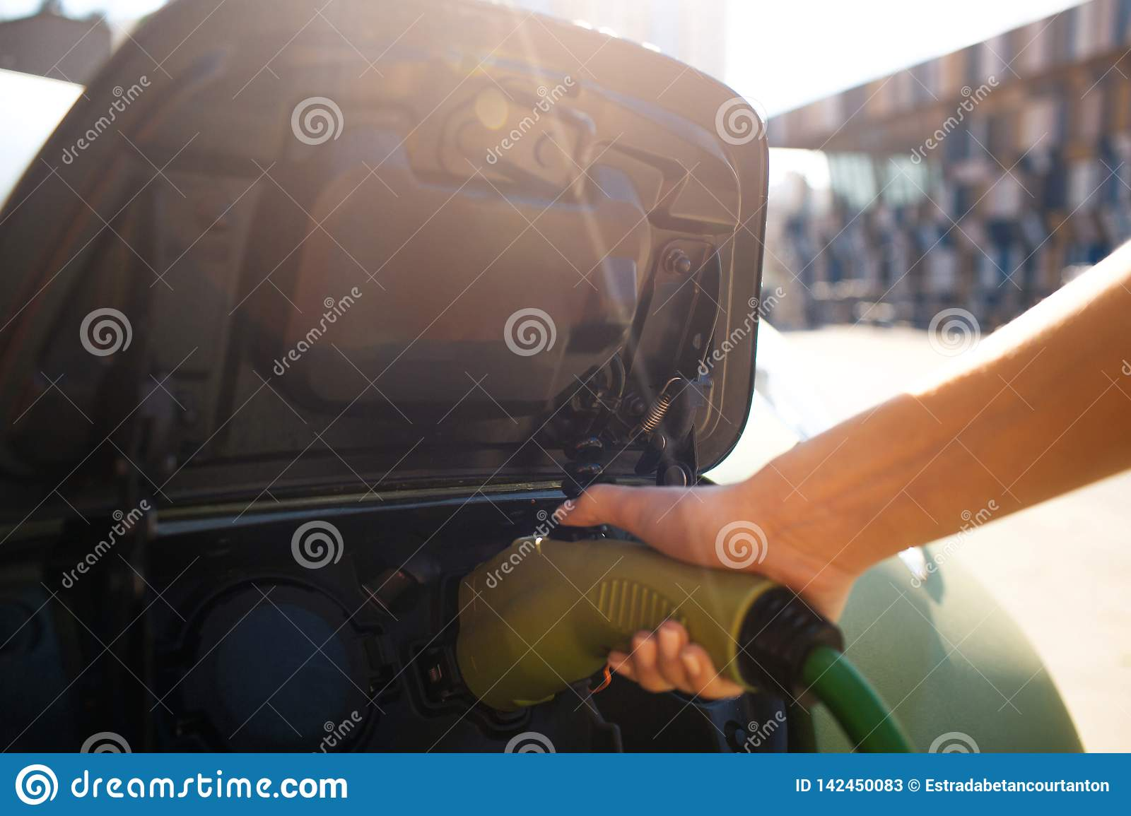 Electric vehicle charging station. Male hand charging an electric car with the power cable supply plugged in. Eco