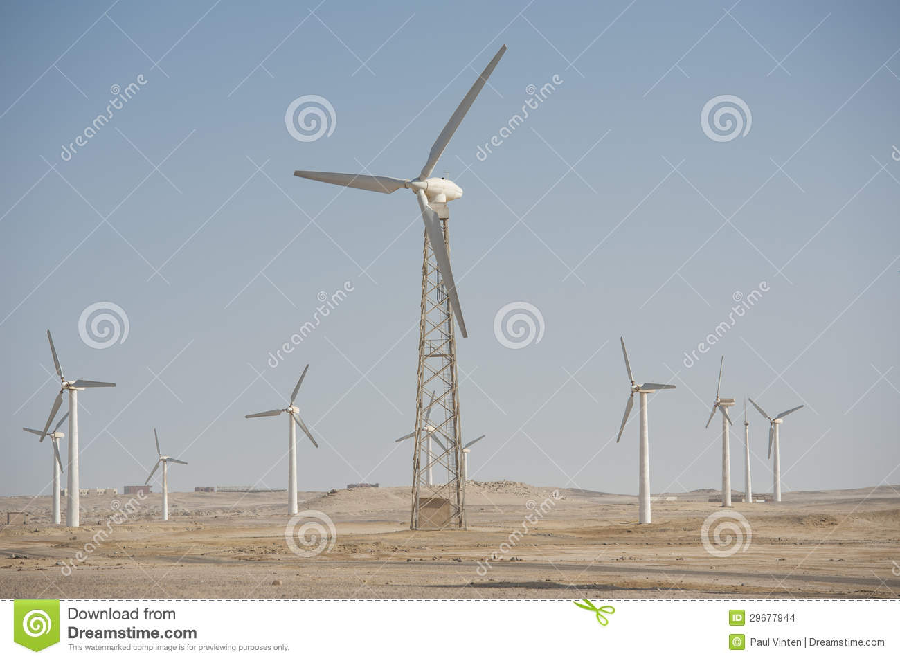 Electric wind turbine generators in the desert against a blue sky ...