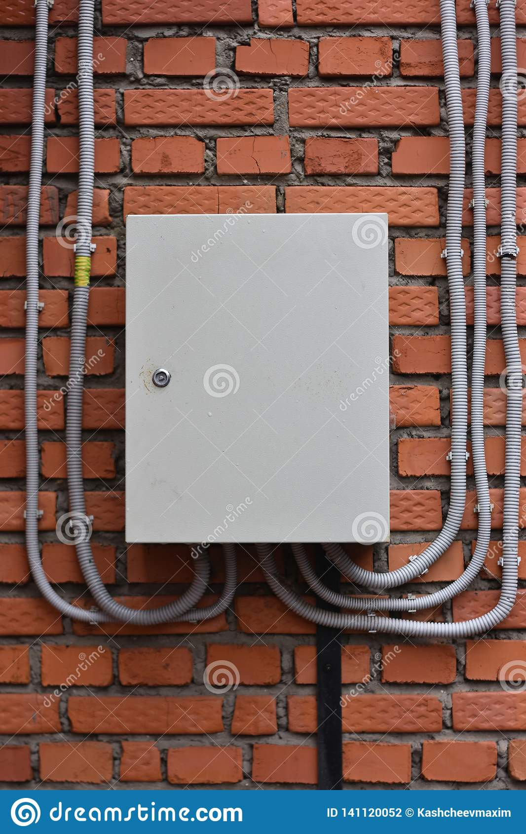 Electrical box on a brick wall. plastic cable channels