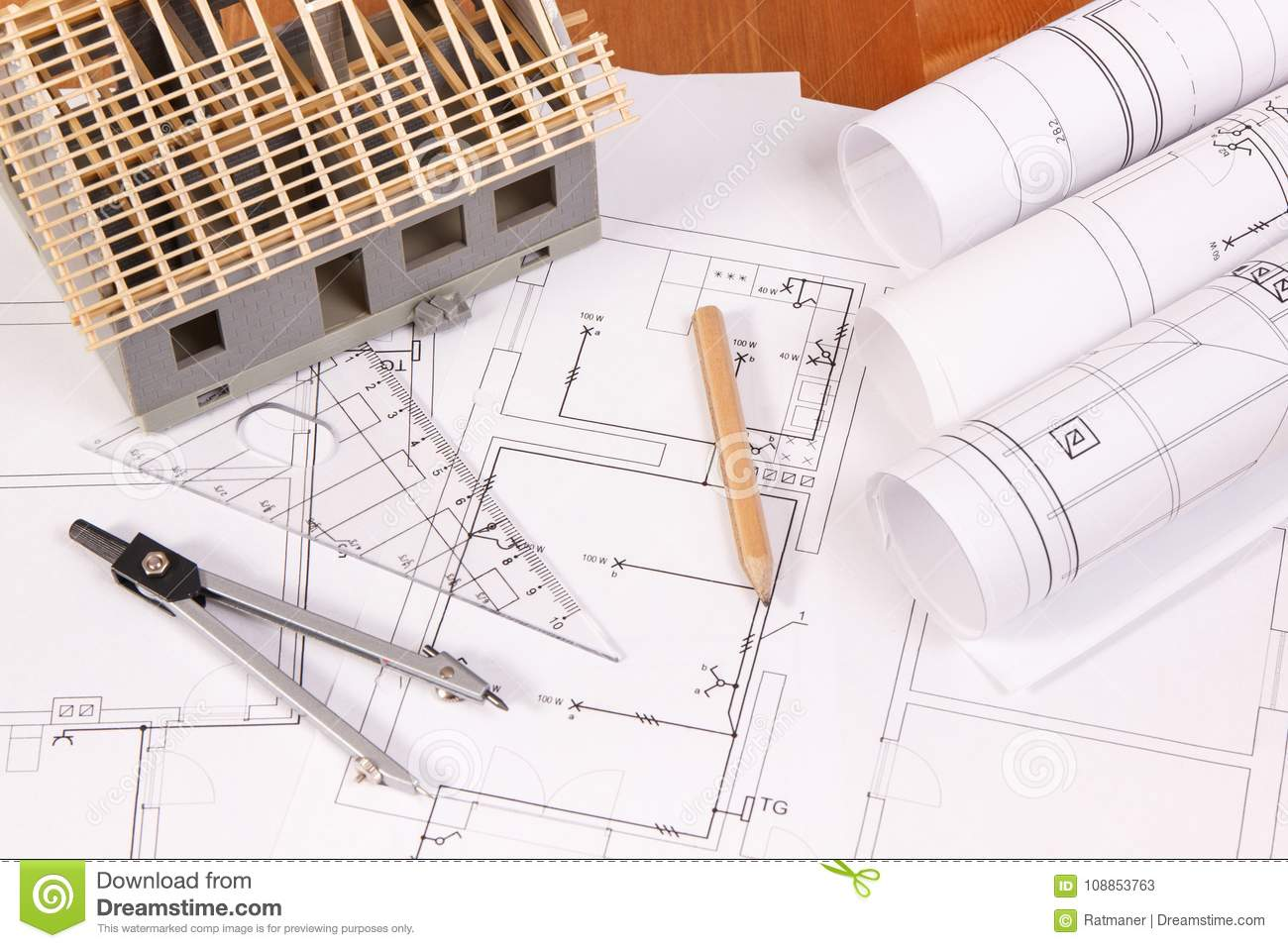 Electrical diagrams, accessories for engineer jobs and house under  construction on desk, building home