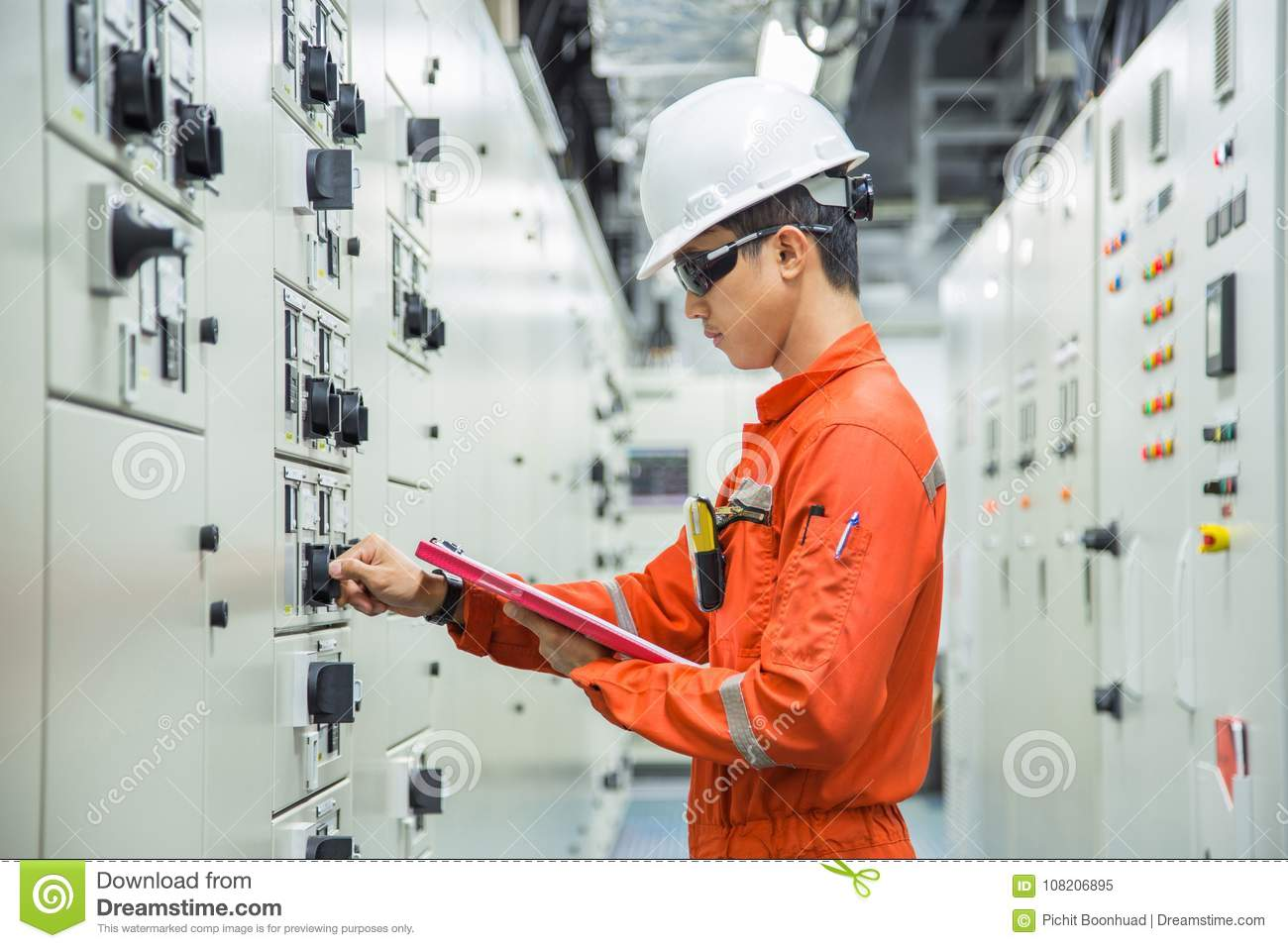 Electrical and Instrument technician checking electrical control board of motor starting system in switch gear room