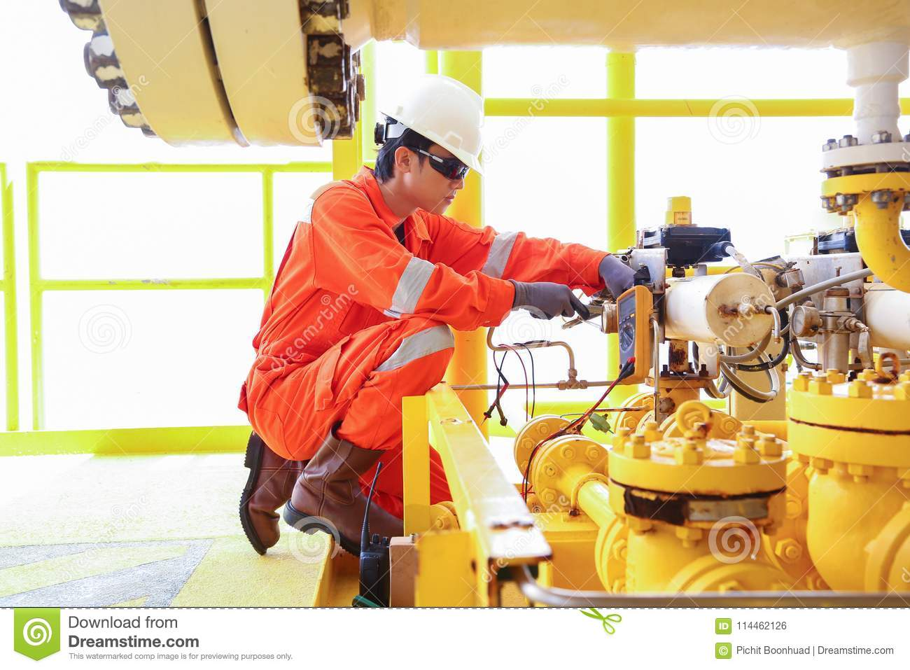 Electrical and instrument worker inspect and checking voltage and current of electric and control system.