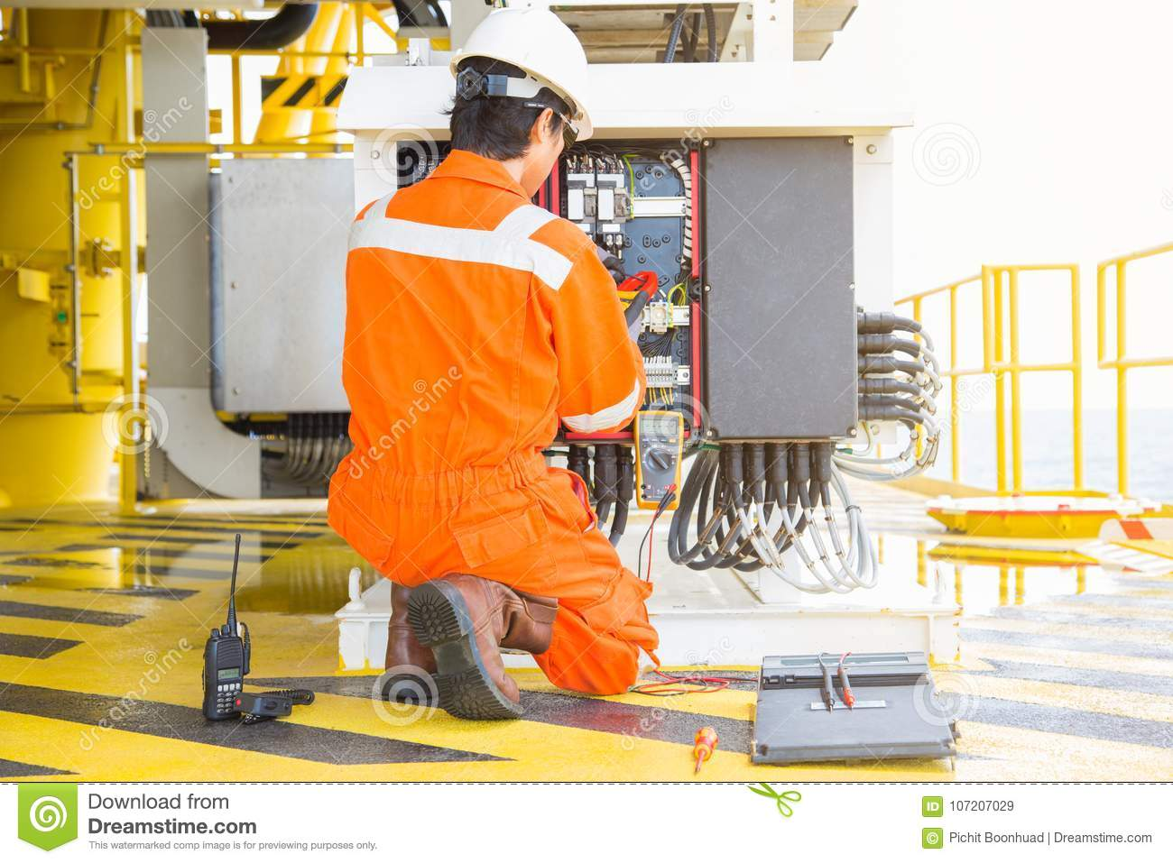 Electrical and instrument worker inspect and checking voltage and current of electric system at oil and gas platform for preventiv