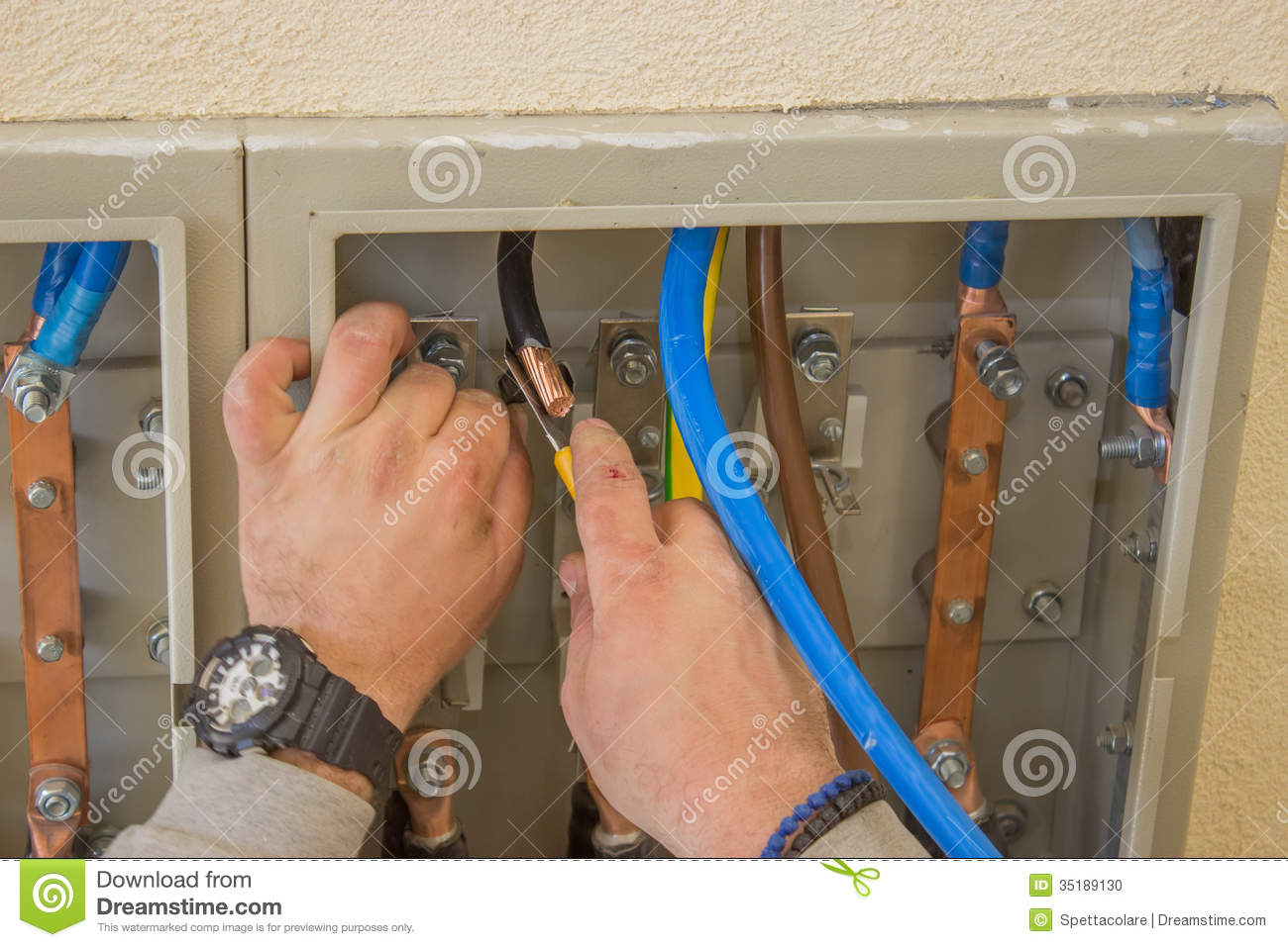 Electrician connecting wires in the electrical cabinet