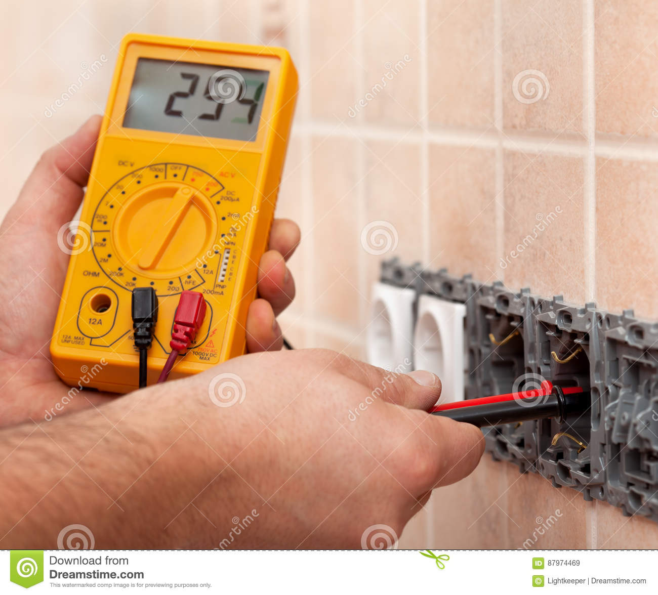 Electrician hands measuring voltage in electrical wall socket wi