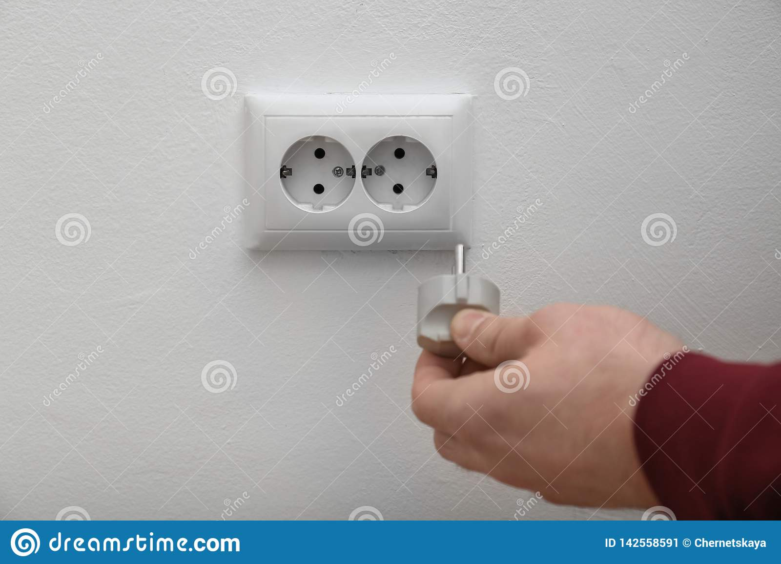 Electrician inserting plug into power socket on white, closeup