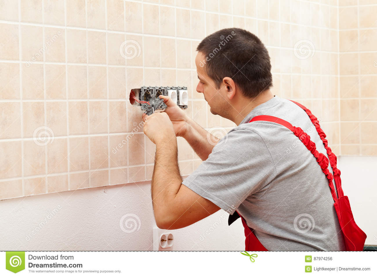Electrician installing electrical wall fixture
