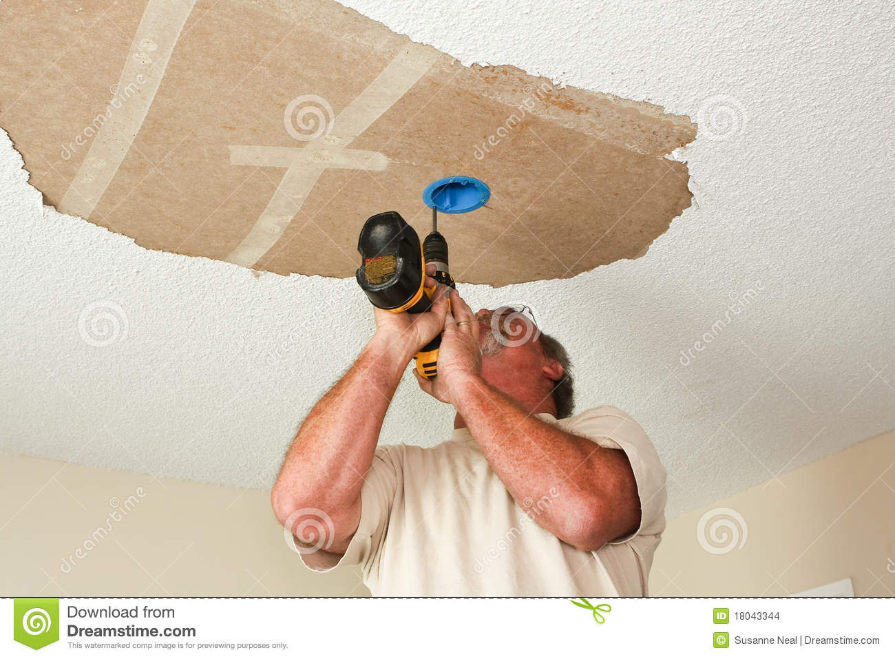 Electrician Installing Light Fixture On Ceiling Stock