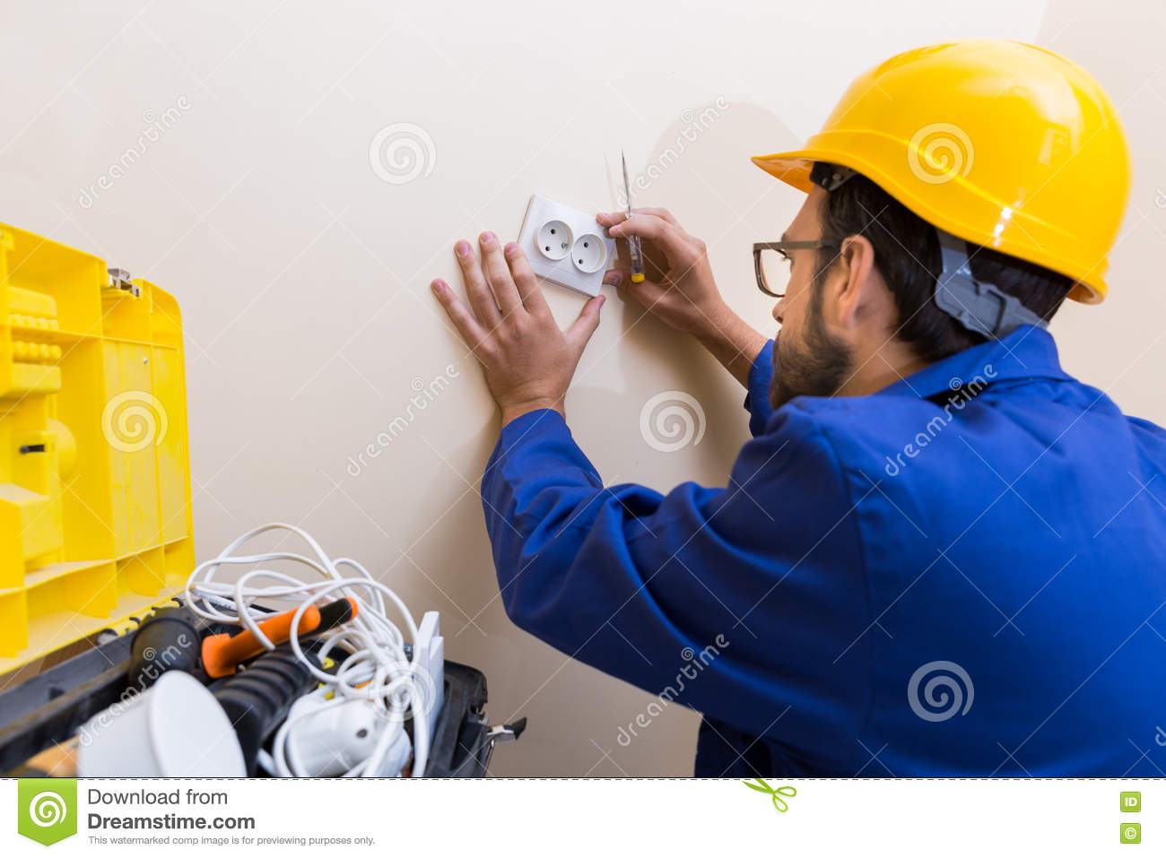 Electrician In Uniform And Hard Hat Working With Electric