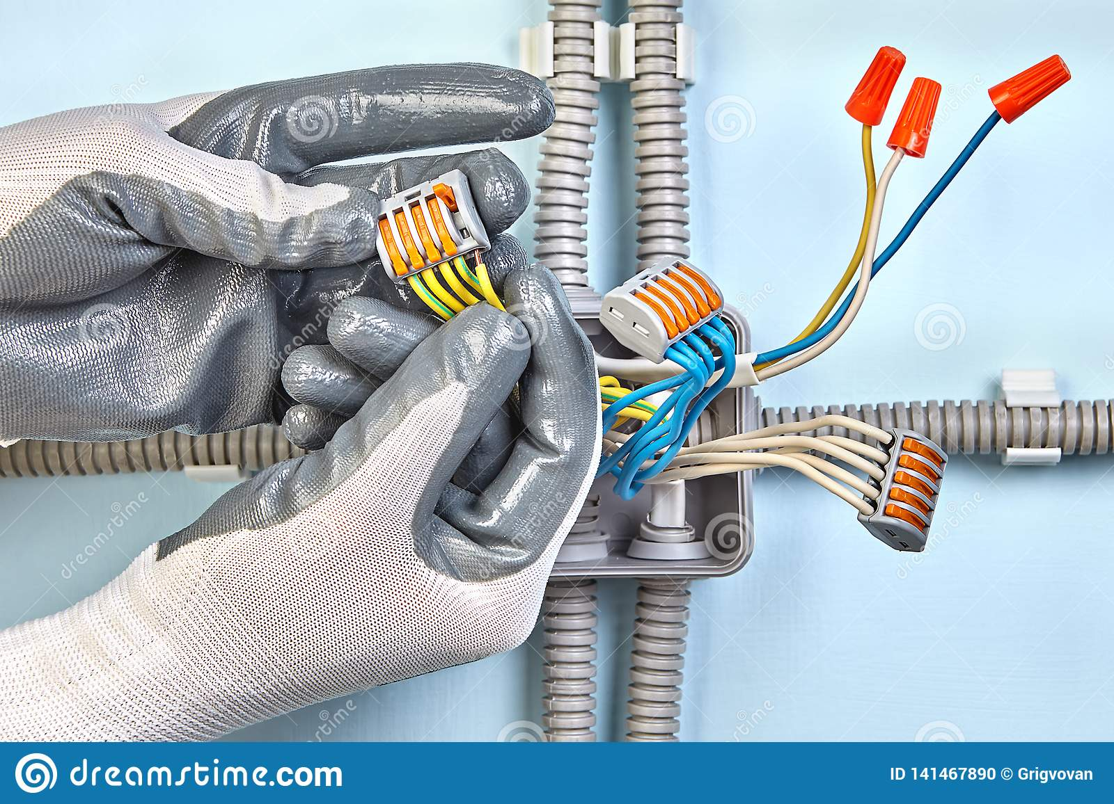 Electrician in protective gloves mounts junction box