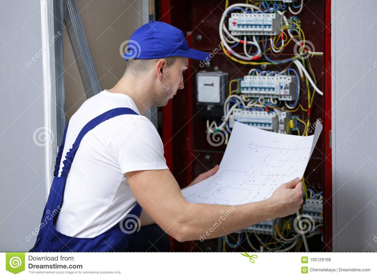 Electrician With Wiring Diagram Checking Connections Stock Photo Distribution Board