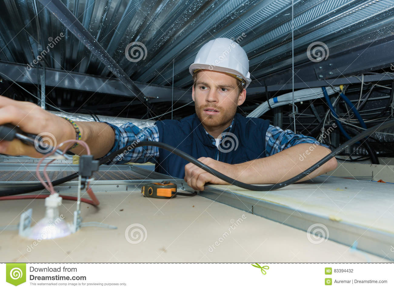 Electrician working with electric wires in factory