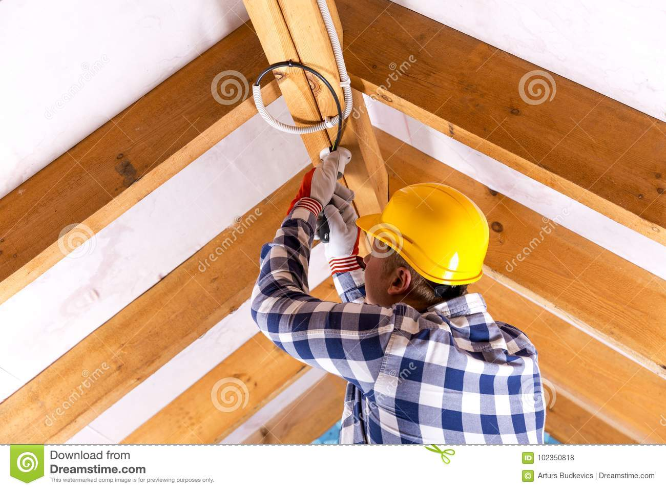 Electrician working with wires at attic renovation site