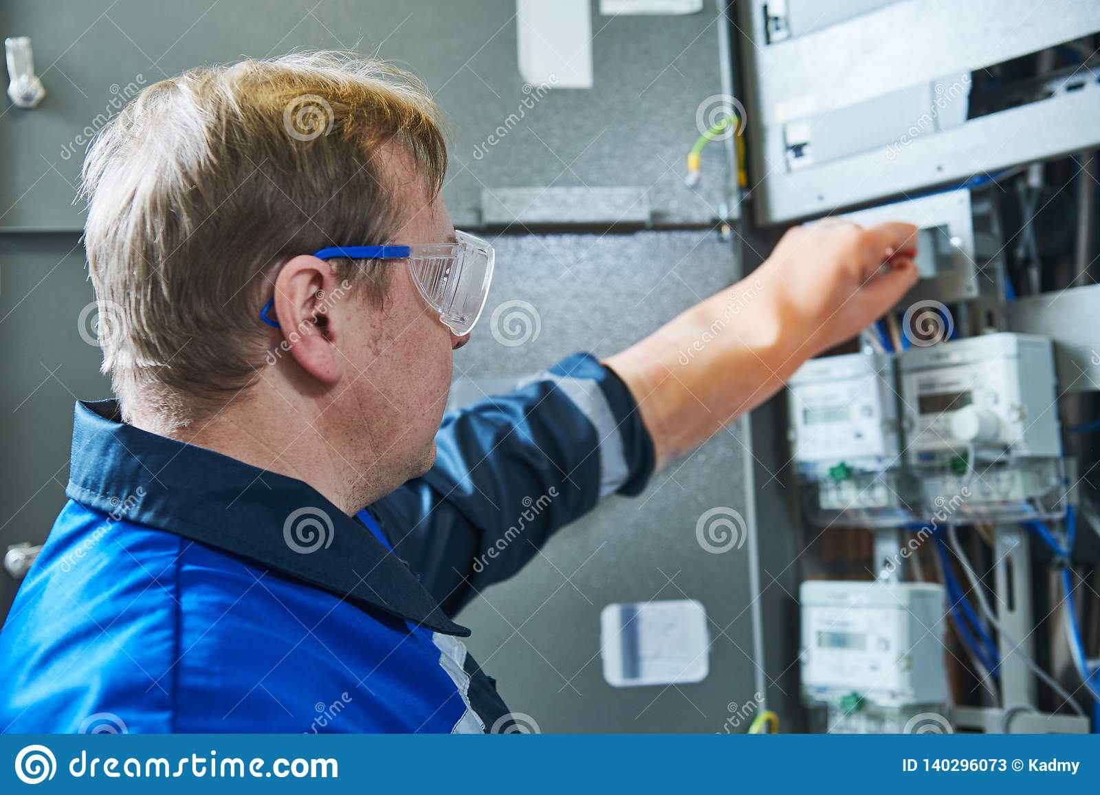 electrician works in fuse box  switching of circuit breaker