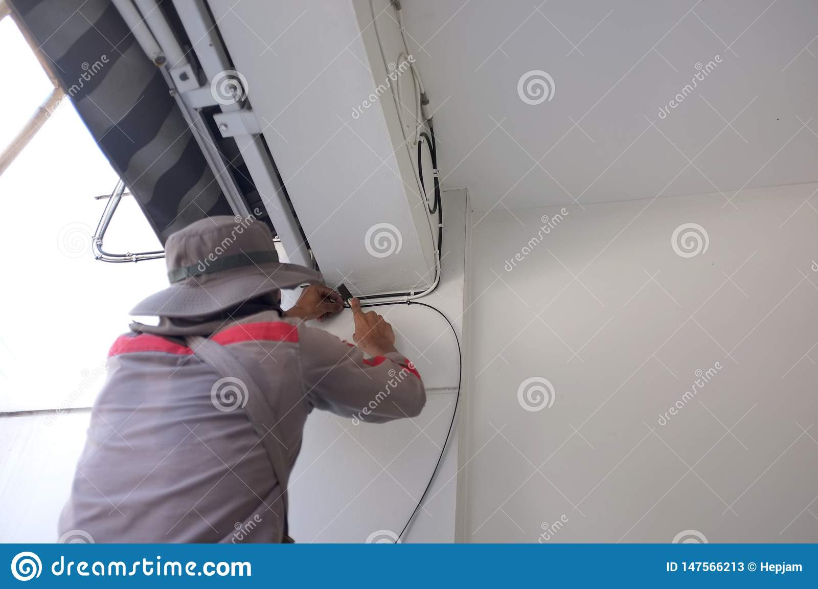 Electricista del emplazamiento de la obra Trabajador con los cables el?ctricos