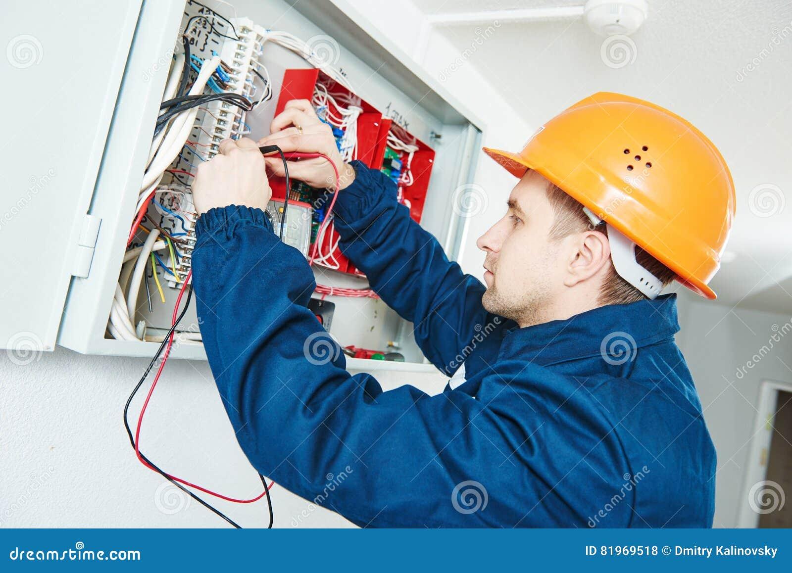 Electricista que examina voltaje actual con el probador del destornillador