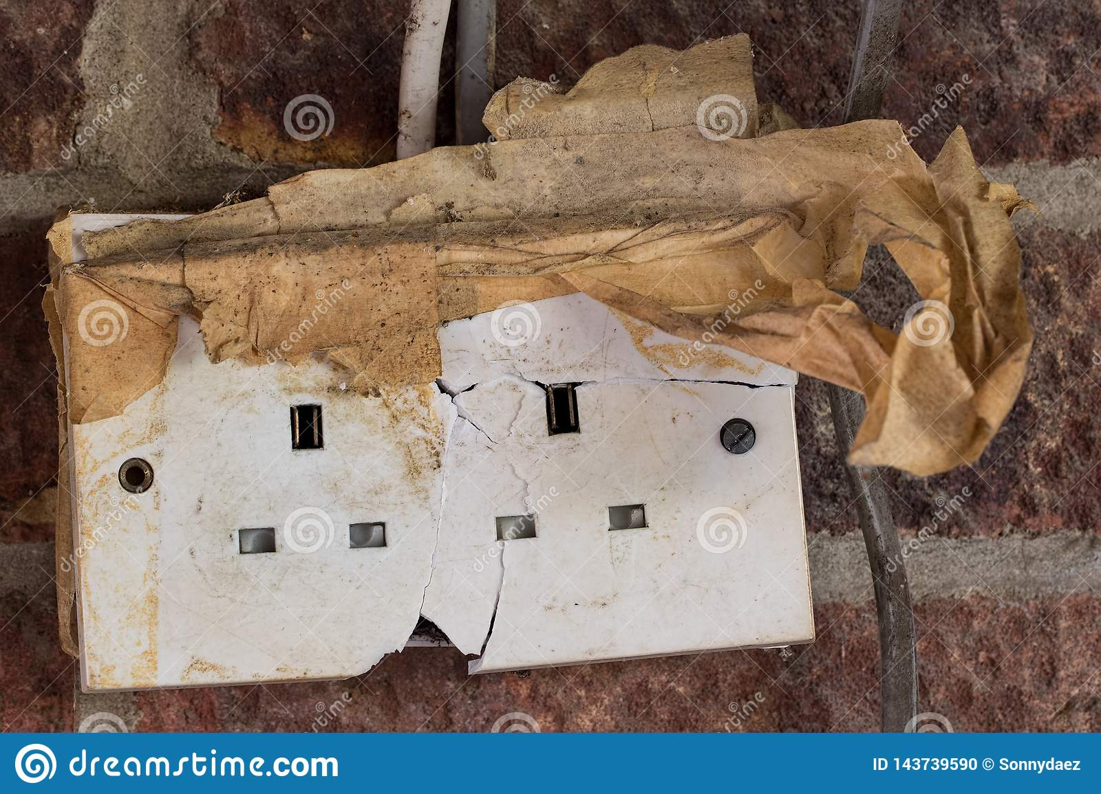 electricity hazard  dangerous cracked and damaged electrical power wall  socket  old home garage broken electric plug wiring and cable