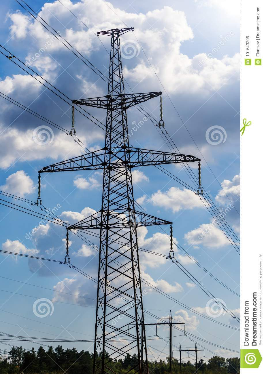 Electricity pylon silhouetted against blue sky background. High voltage tower