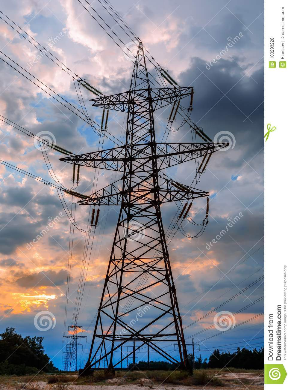 Electricity transmission pylon silhouetted against blue sky at dusk.
