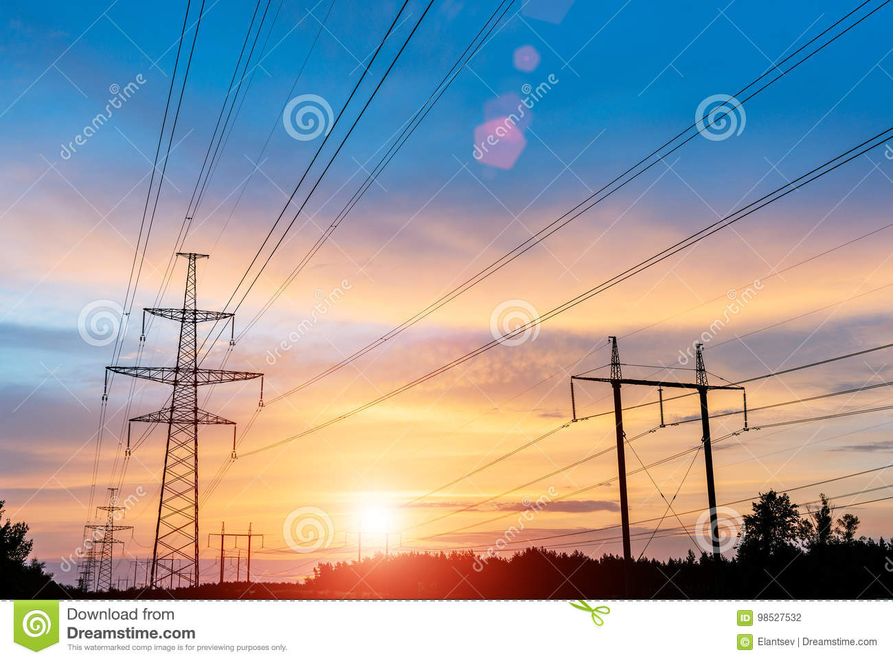 Electricity transmission pylon silhouetted against blue sky. high voltage post.