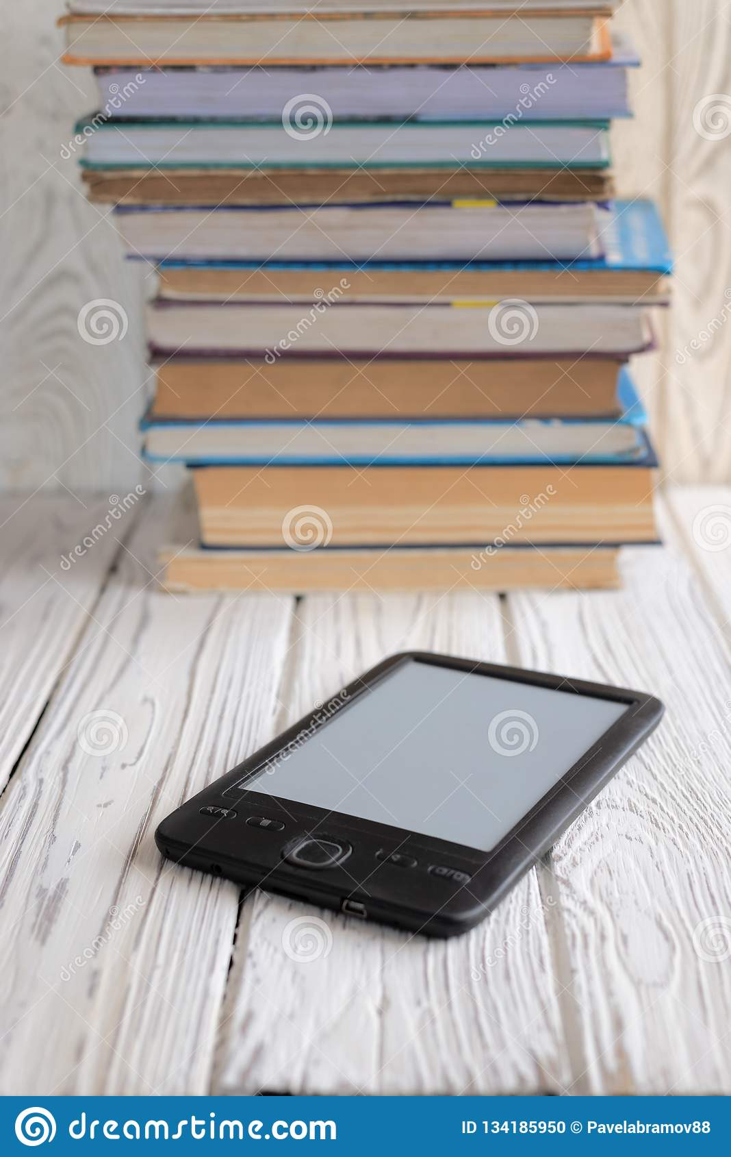 Electronic book shown versus several regular text books