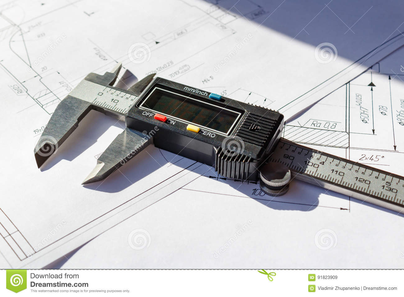 Electronic caliper lies on a engineering drawings