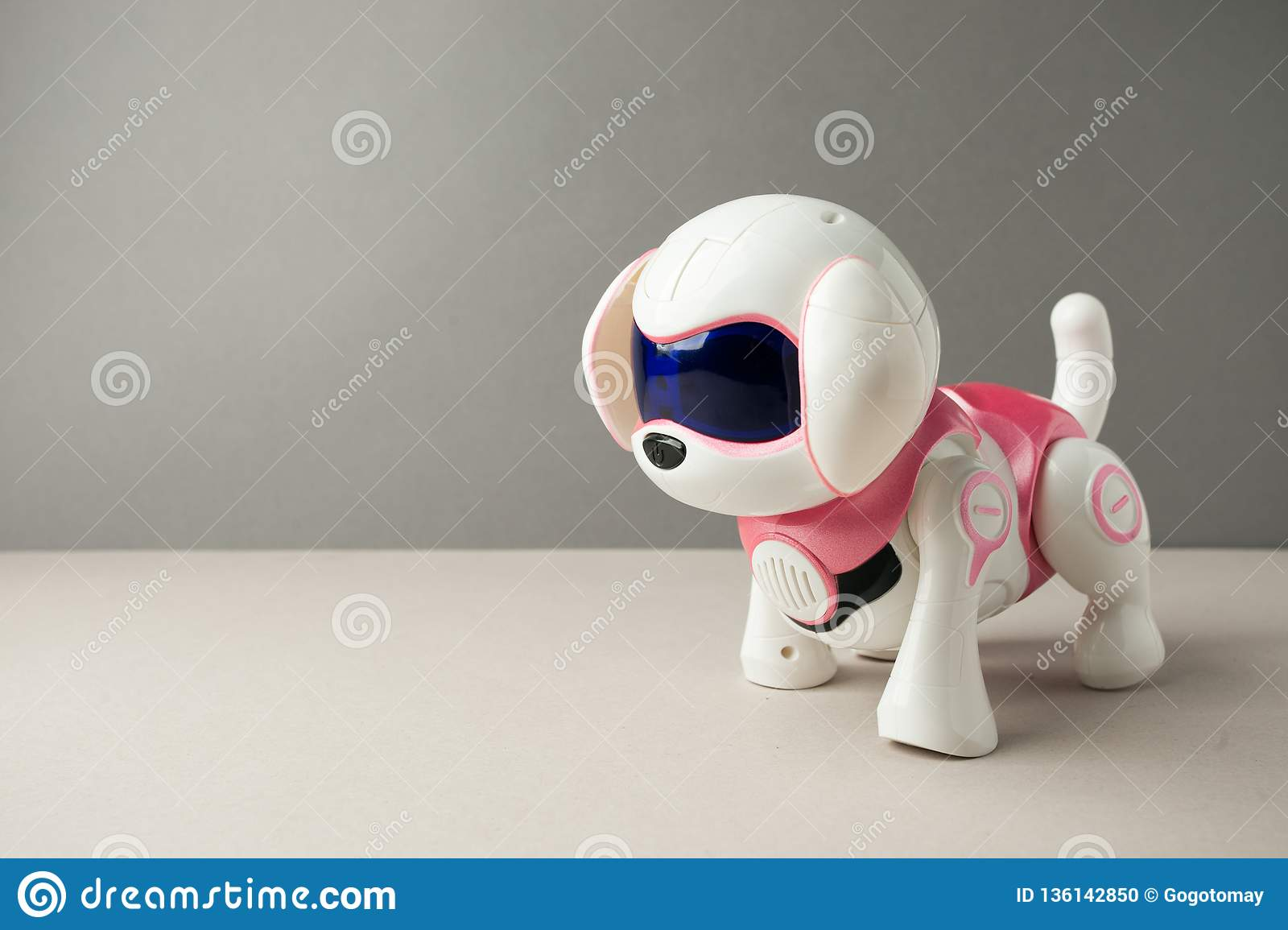 Electronic interactive toy dog puppy on a gray background, high technology concept, pet of the future, electronic home, copy space