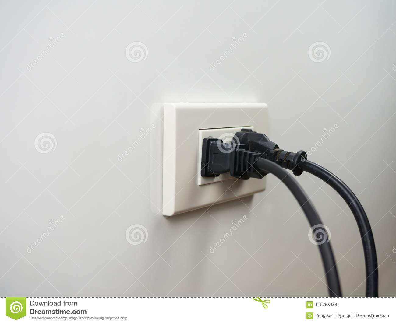 Electronics plugged in to the socket on white wall