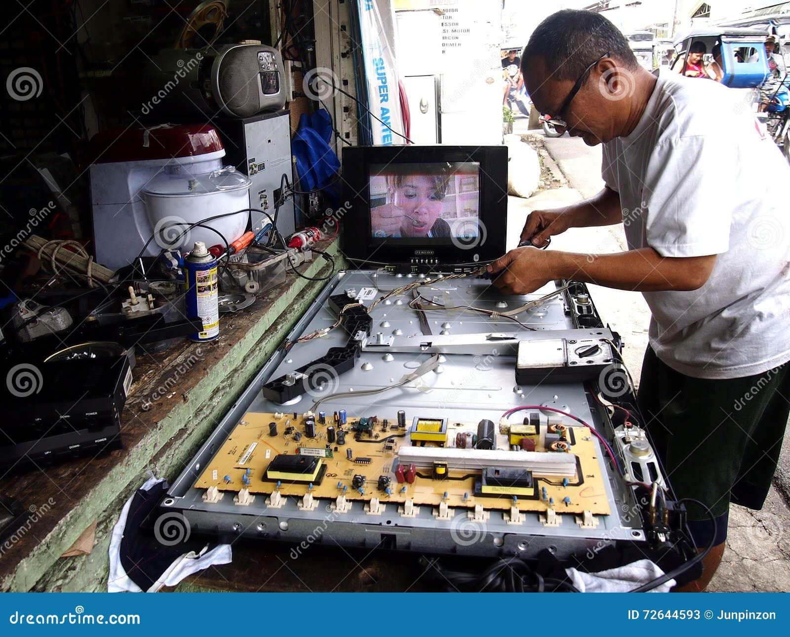 An electronics repair shop technician works on a flat screen tv.