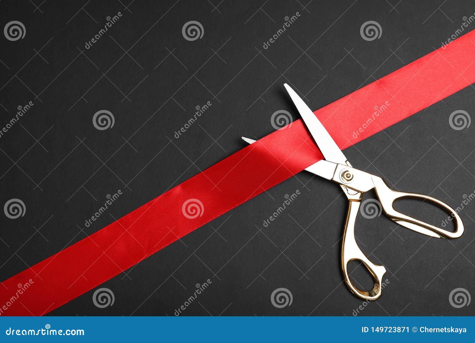 Eleganccy nożyce i czerwony faborek na czarnym tle, przestrzeń dla teksta Ceremonialny taśmy rozcięcie