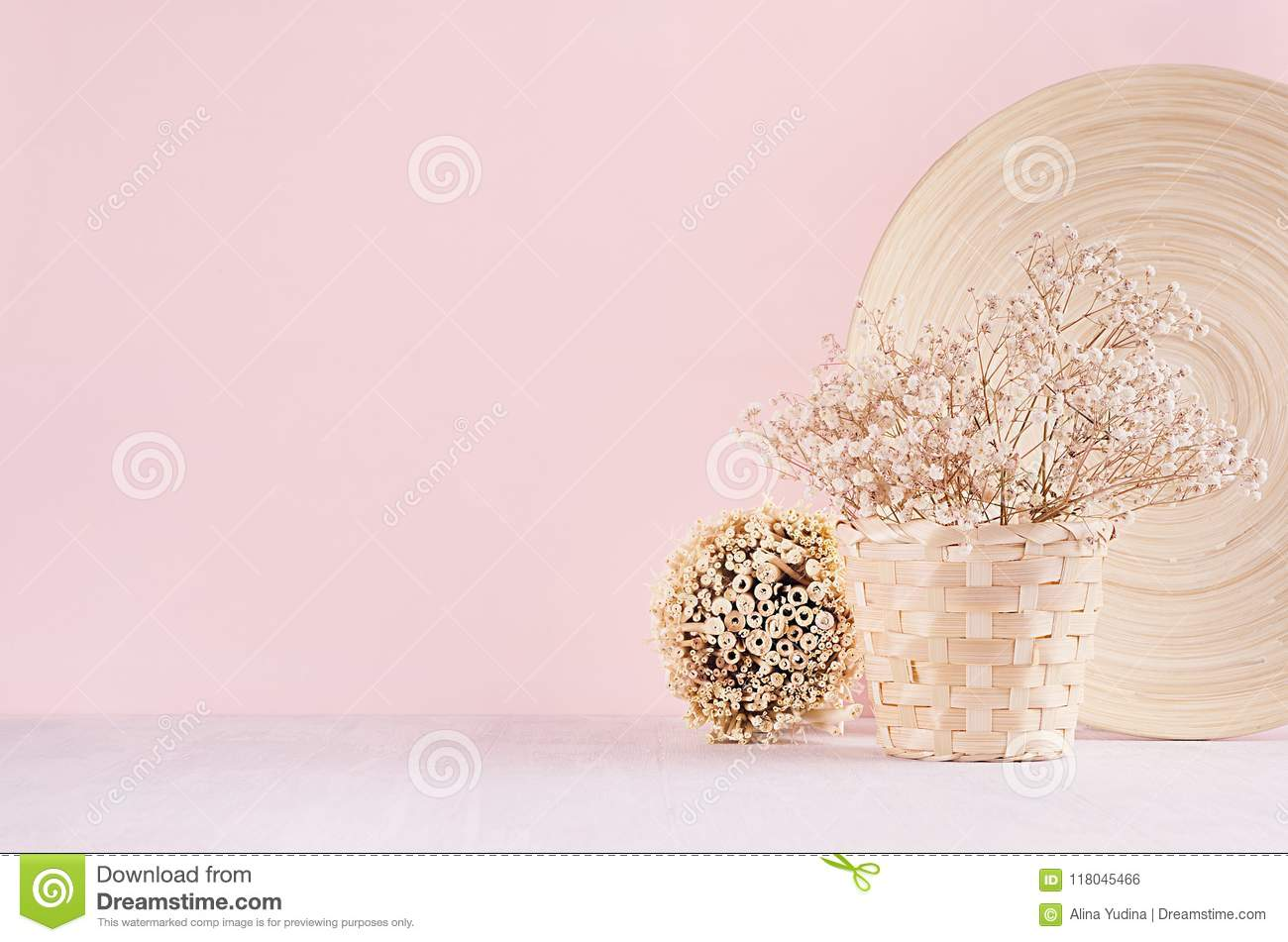 Elegance home eco decor - white dried flowers bouquet in basket with decorative plate, bunch sticks on fashion pink background.