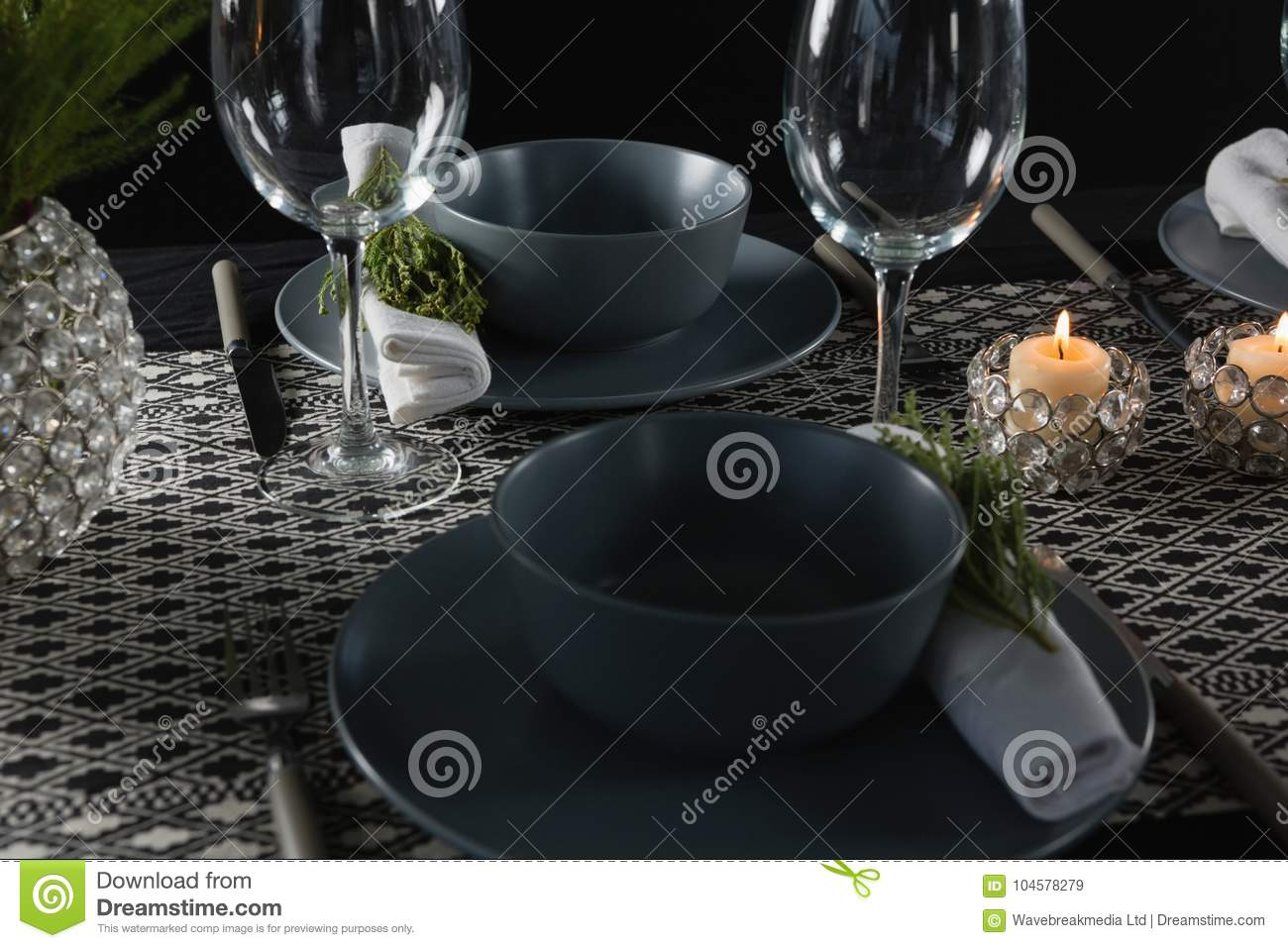 Elegance table setting with empty wine glasses and lit candle