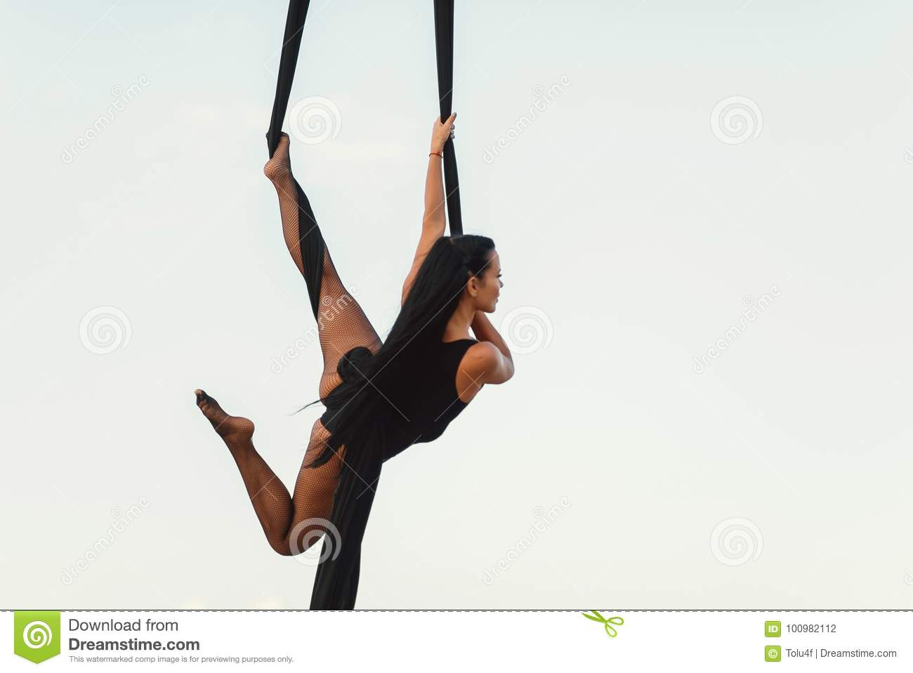 Elegance young beautiful woman dance with aerial silk on a sky background. Fly yoga sport