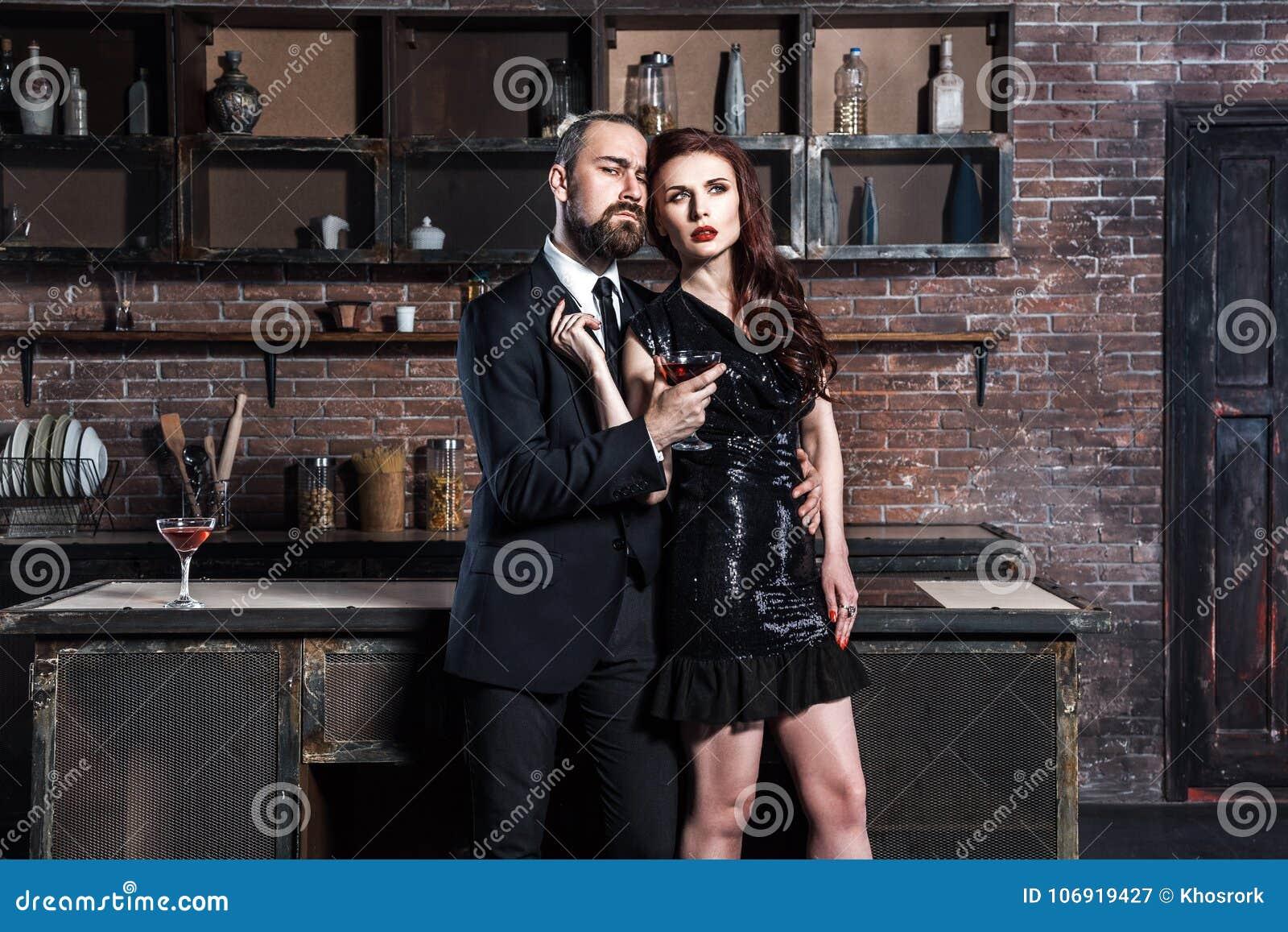 Elegancja przyjaciele pozuje na kuchni, trzyma szkła winograd