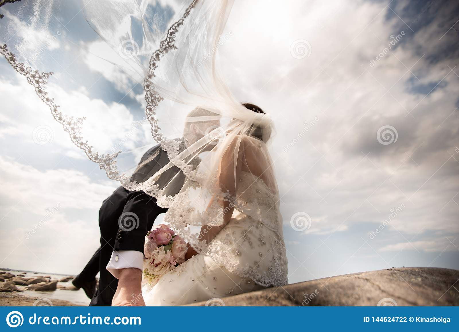 Elegancka ślub pary pozycja na dennym brzeg Nowożeńcy chodzą morzem