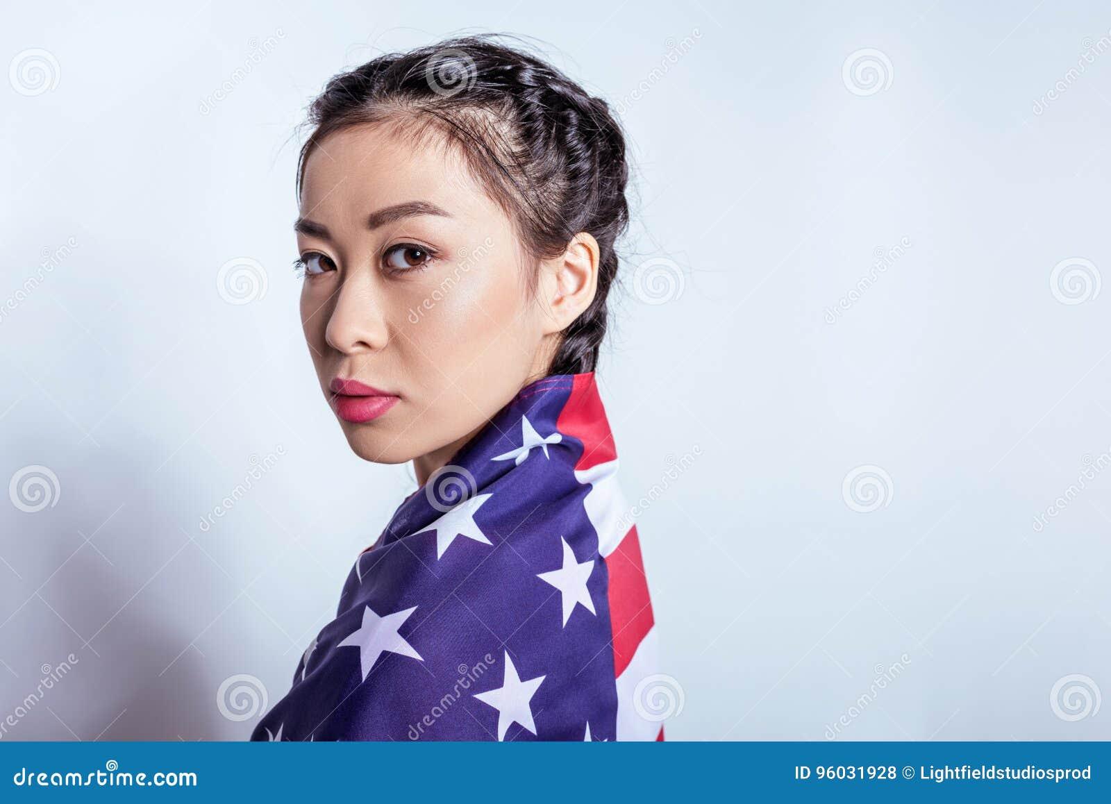 Elegancka azjatykcia dziewczyna zawijająca w flaga amerykańskiej patrzeje kamerę odizolowywającą na popielatym