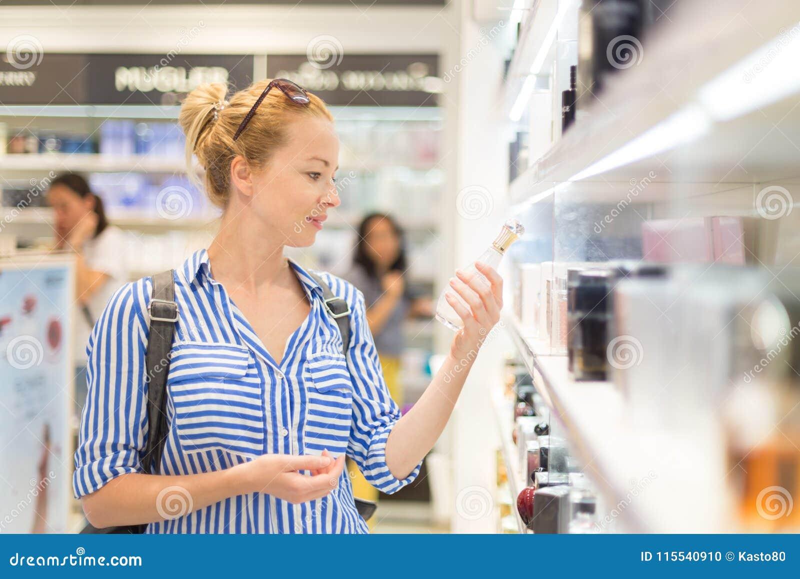Elegancka blond młoda kobieta wybiera pachnidło w sklepie detalicznym