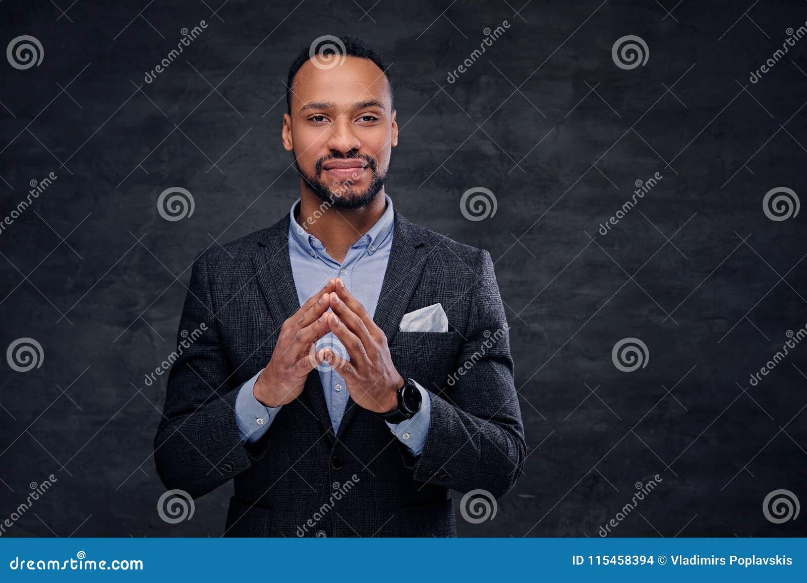 Elegancka czarna samiec ubierał w kostiumu nad popielatym tłem