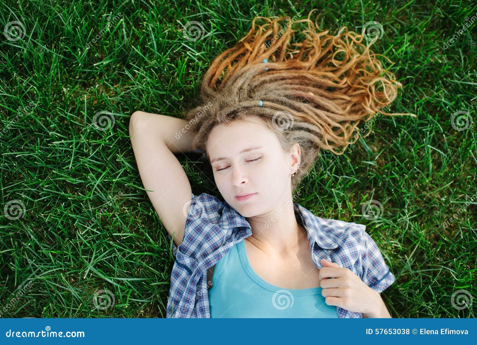 Elegancka dziewczyna kłama na zielonej trawie z dreadlocks